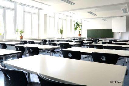 Ein leerer Schulungsraum mit hellen Tischen und schwarzen Stühlen. Aufstellung in drei Reihen mit jeweils mehreren Tischen hintereinander und jeweils zwei Sitzplätzen.