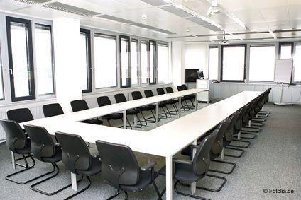 Ein leerer Seminarraum mit hellen Tischen zu einer U-Form aufgestellt und schwarzen Stühlen.